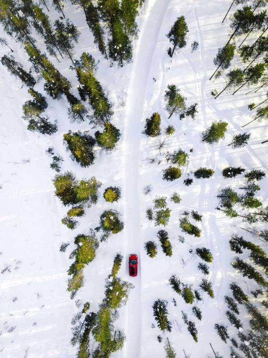 aerial-view-of-red-car-driving-through-the-white-s-NBZCPLJ-scaled.jpg